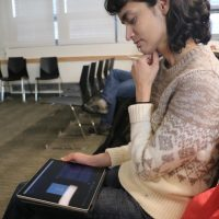 Female student sitting looking at a tablet with captions